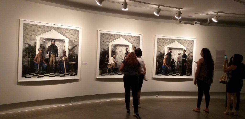 Fotografia da exposição ExAfrica com 3 quadros grandes alinhados lado a lado e algumas pessoas apreciando.