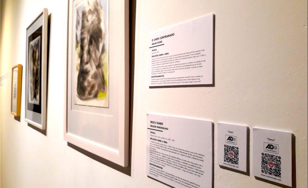 Fotografia aproximada da ficha técnica de quadros expostos na parede. Em detalhe qrcode de audiodescrição com a logomarca cinemacego.