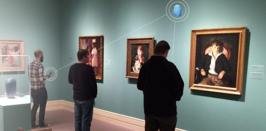 Fotografia de três homens lado a lado em exposição de arte com três quadros a mostra. No alto da parede da exposição está o dispositivo beacon que envia a audiodescrição para os celulares dos visitantes via conexão bluetooth.