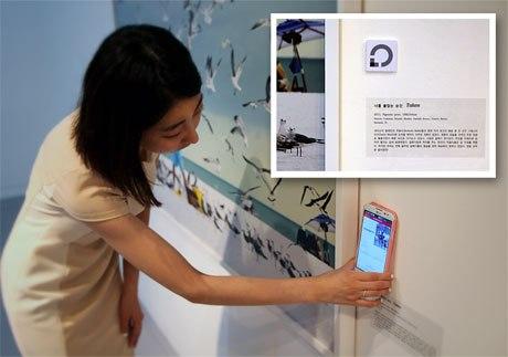 Fotografia de mulher aproximando o celular da ficha técnica de quadro em exposição. Detalhe aproximado da da ficha técnica e dispositivo com chip de aproximação NFC.