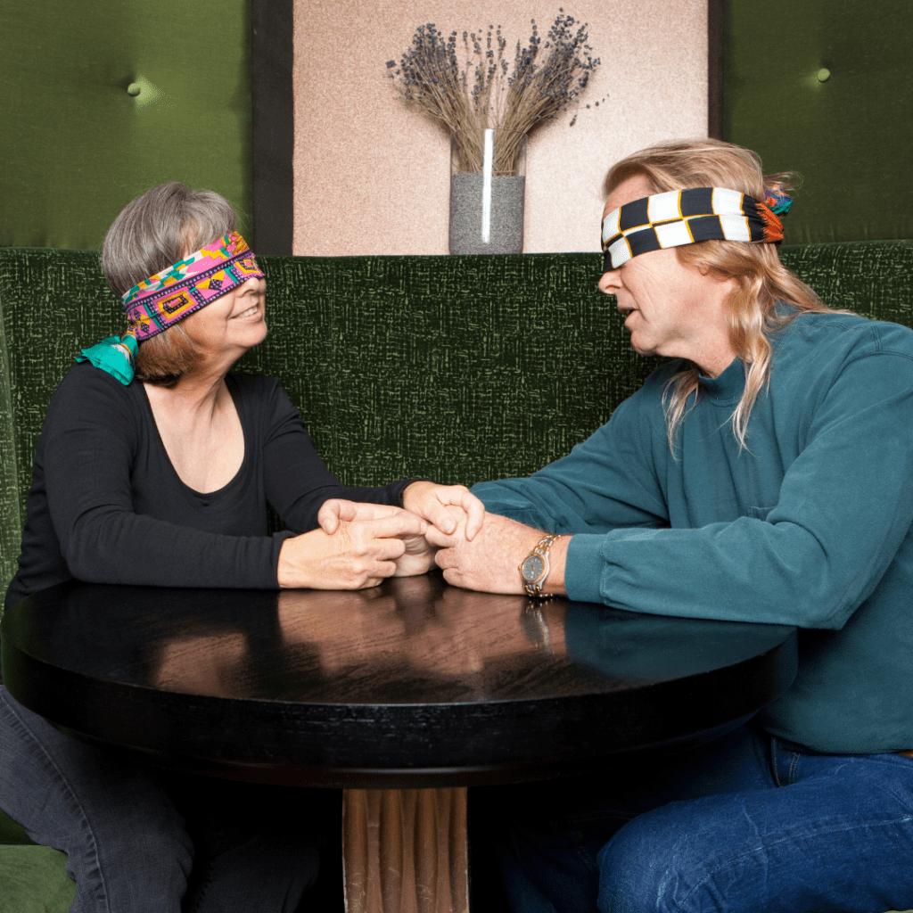 Fotografia de um casal de olhos vendados, sentados em uma mesa redonda de restaurante.