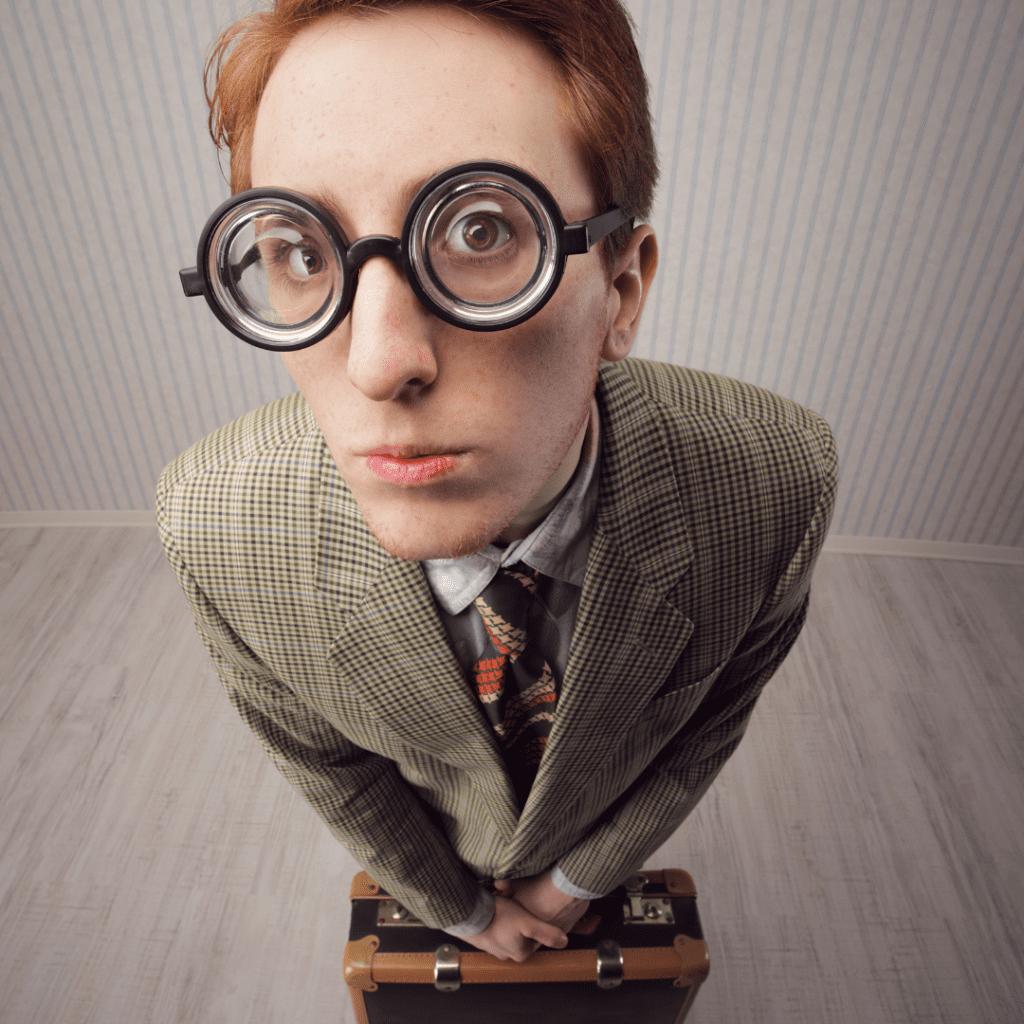 Fotografia tirada de cima para baixo, de um jovem ruivo com óculos de armação preta e lentes grossas fazendo cara de dúvida. Ele usa terno e gravata e segura uma maleta com as duas mãos a frente do corpo.