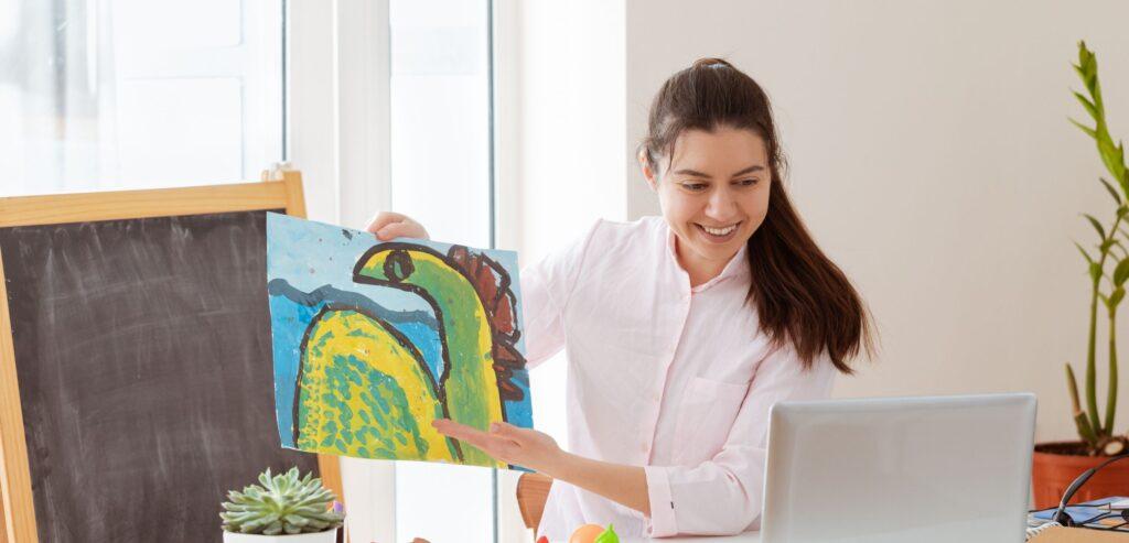 Fotografia colorida de uma professora segurando um cartaz com o desenho de um dinossauro, à frente do computador.