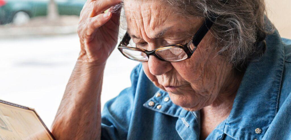 Fotografia colorida de uma idosa lendo um cardápio. Ela tem aproximadamente 70 anos, usa óculos e está com a mão direita na cabeça, em sinal de preocupação.