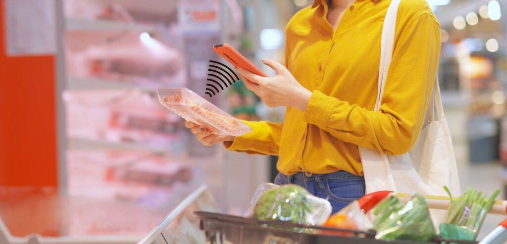 Fotografia de uma mulher apontando a câmera do celular para o QRCode de um produto de consumo.
