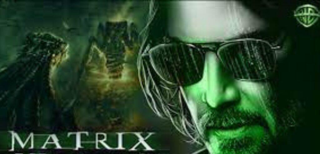 Banner do trailer de Matrix Ressurrection. A imagem está em preto e branco e tem um filtro verde. Neo está mais velho, tem os cabelos lisos pretos e compridos, na altura da orelha. Usa um óculos escuros e barba.
