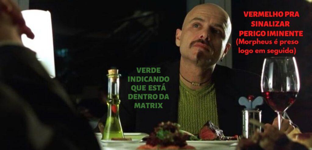 Imagem com o texto: Verde indicando que está dentro da matrix e vermelho para sinalizar perigo iminente (Morpheus é preso em seguida). Logo abaixo, cena de Cypher no restaurante. Ele é careca, usa um blazer preto e camiseta verde por baixo. Na mesa, logo a sua frente, à esquerda, uma garrafa de azeite verde. Ao lado um prato branco com um bife alto, suculento e sangrento. À direita, uma taça de vinho tinto.