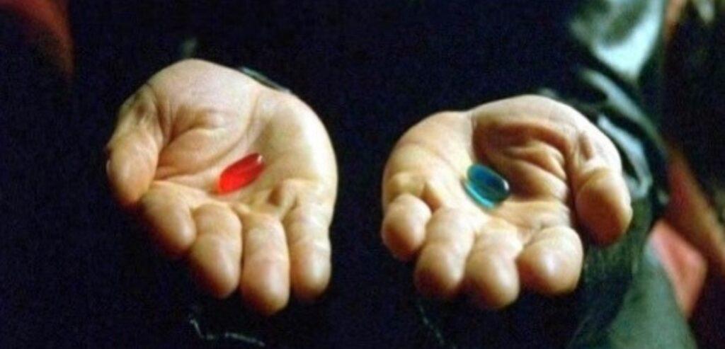 Cena de Matrix com o foco nas mãos de Morpheus. Na esquerda, tem uma pílula azul e na direita, uma pílula vermelha.