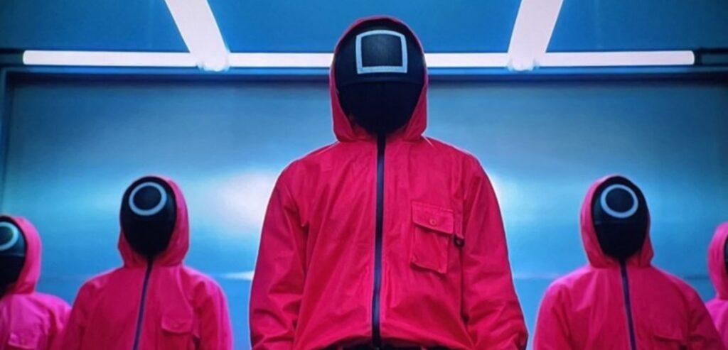 Imagem de Round seis, com 3 guardas à frente de uma parede azul. Eles usam macacão rosa-choque com capuz e máscara preta tampando todo o rosto. Na testa do personagem que está no meio, há o desenho de um quadrado branco. Nos dois que estão ao lado, há um círculo.