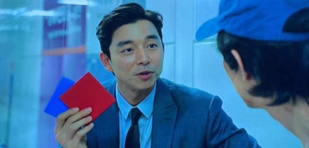 Cena de Round seis em que o personagem principal está de frente a um vendedor que lhe mostra um cartão azul e outro vermelho. A cena usa um filtro azul e o personagem principal também usa um boné azul.