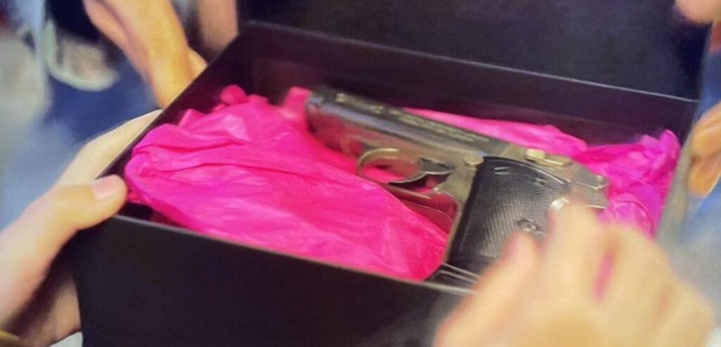 Cena de Round seis, com uma caixa de presente preta com um revólver dentro. O papel de embrulho da arma é rosa-choque.