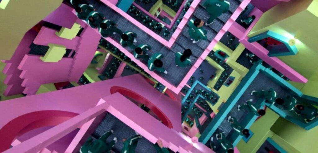 Cena de Round seis com um corredor com escadas em formato de labirinto. O local tem paredes rosas, verdes e alguns detalhes em amarelo.