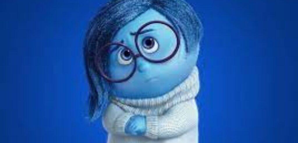 Imagem da personagem Tristeza, do filme Divertidamente. Ela é azul, tem o cabelo curto, liso, na altura da orelha, jogado para o lado. Usa um casaco branco e óculos de grau de armação redonda. O semblante dela é de tristeza.