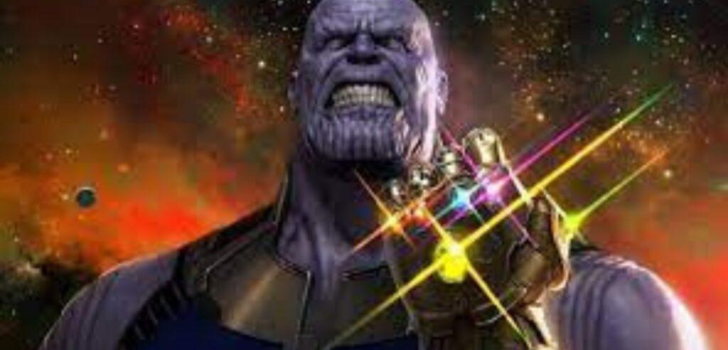 Imagem de Thanos, do filme Vingadores. Ele é grande, fortão e todo roxo. Em primeiro plano, mostra a sua manopla com as cinco joias do infinito. Uma das pedras é roxa.